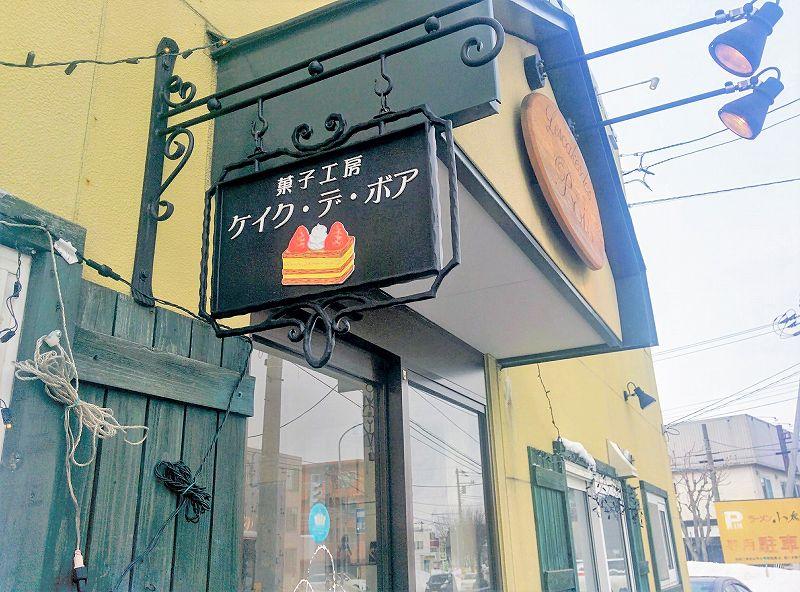 いちごのミルフィーユの絵が描かれた、菓子工房ケイクデボアの店名看板