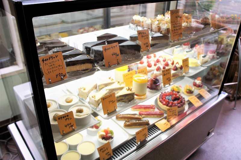 20種類以上のケーキやプリンがガラスのショーケースに入れられているようす