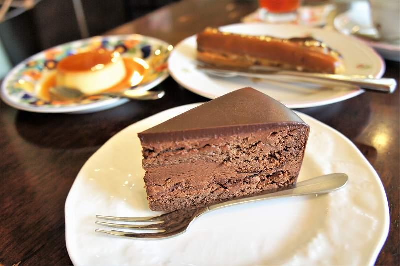 チョコレートケーキ、プリン、エクレアがのったお皿がテーブルに置かれている