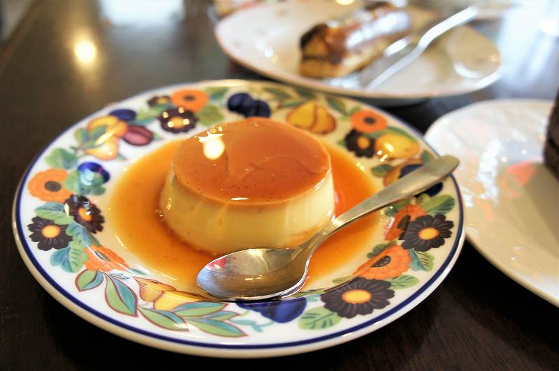 プリンがのせられた花柄のお皿などがテーブルに置かれている
