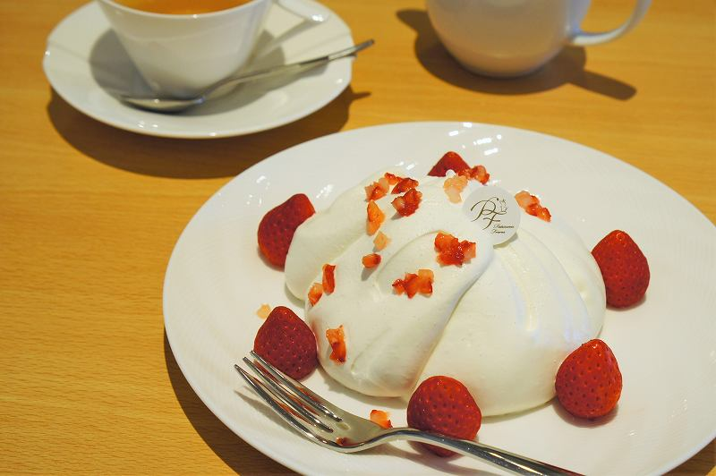 生クリームにおおわれた苺のケーキと紅茶が、テーブルに置かれている