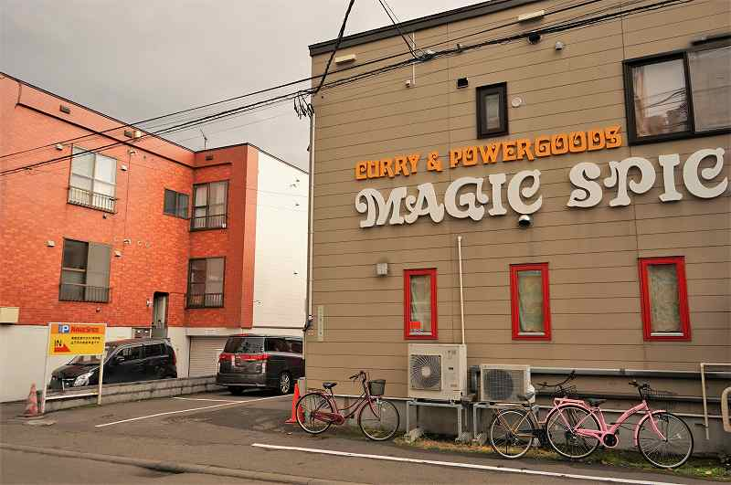 マジックスパイス 札幌本店の店舗側面と、店舗裏の駐車場入口の様子
