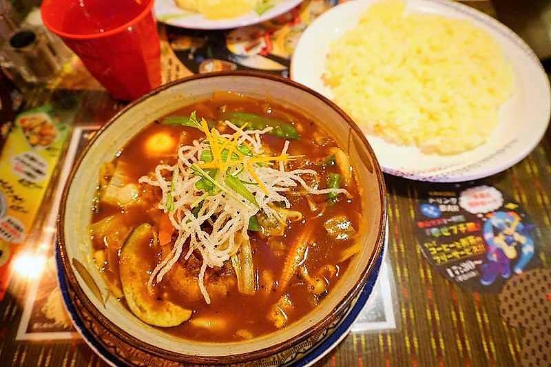 マジックスパイスのハンバーグの入ったスープカレーとライスが、テーブルに置かれている
