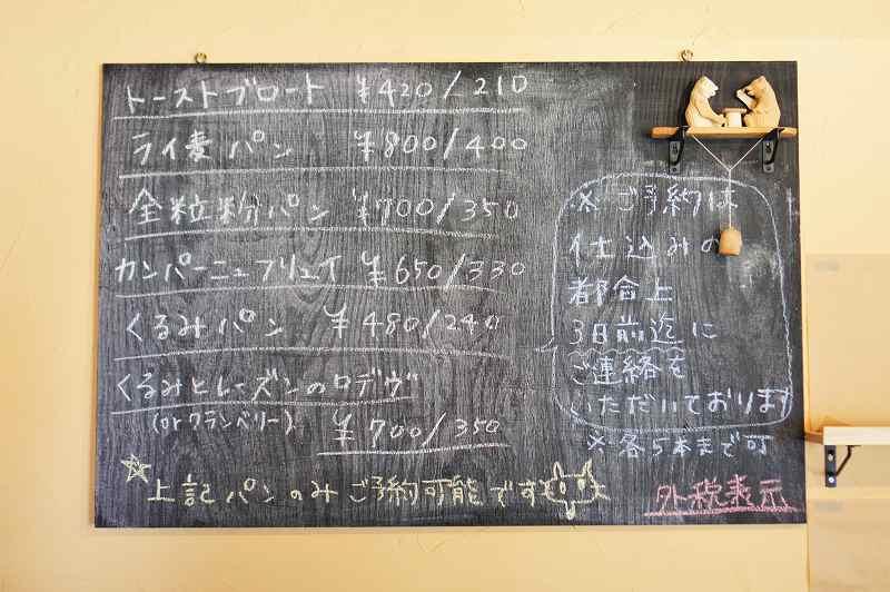 壁に貼られた黒板にメニューが書かれている