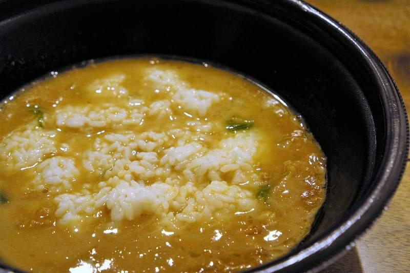 家系カレーラーメンのスープの中でおにぎりをくずしたようす