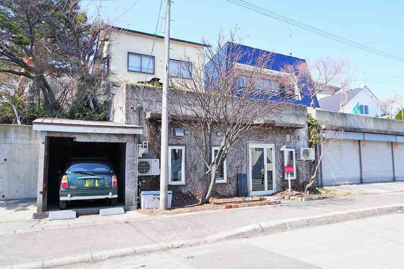 外壁にツタがはっているコンクリート造りの建物と車