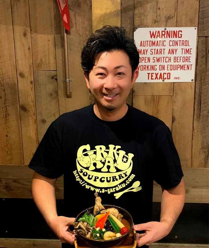 ガラクのオーナー 福生 雅寿さんがスープカレーを持って笑顔で立っている