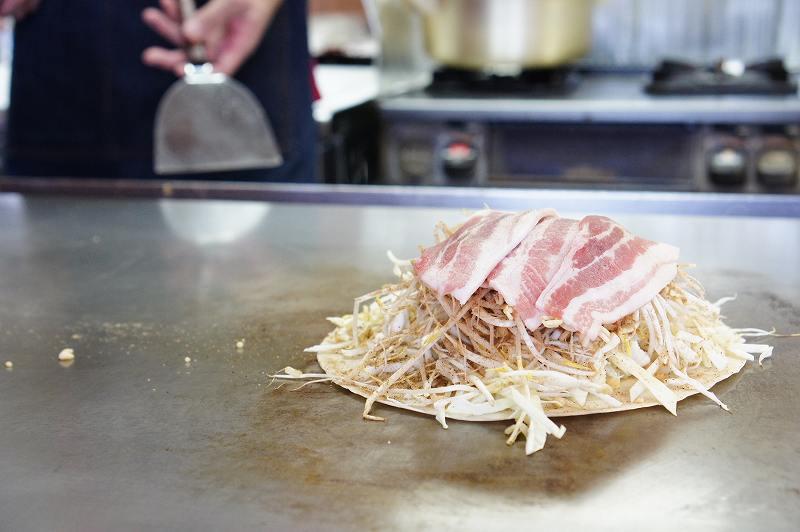 鉄板の上で焼かれている広島お好み焼き