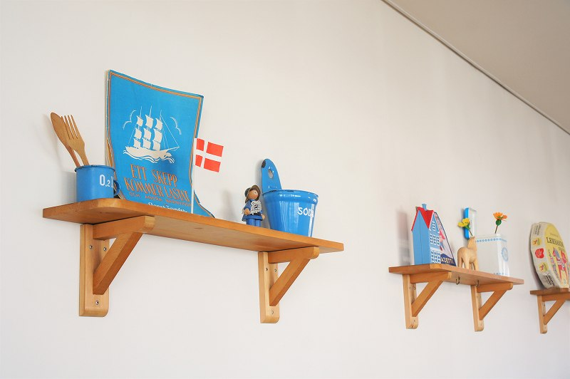 フィンランドの国旗やオブジェが壁の棚に飾られている