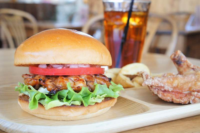 ふっくら肉厚なハンバーガー、チキン、ポテトのプレートとドリンクがテーブルに並ぶ