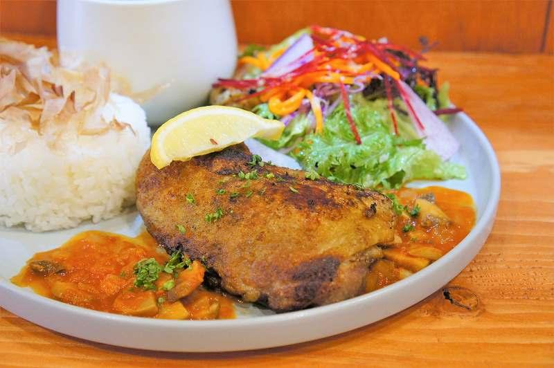 こんがり焼かれたチキンとサラダがのったプレートがテーブルに置かれている