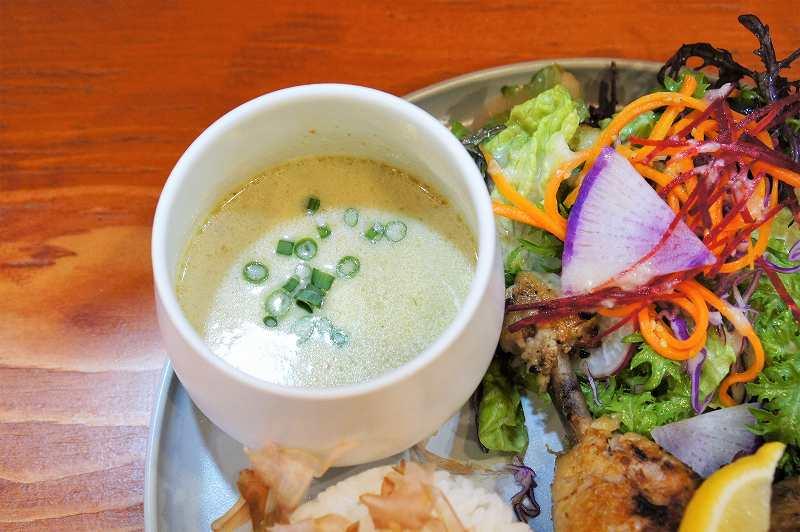 グリーンカレーが入った器とサラダがのったプレートがテーブルに置かれている