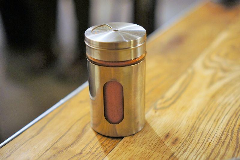 シルバーの入れ物に入ったスパイスがテーブルに置かれている