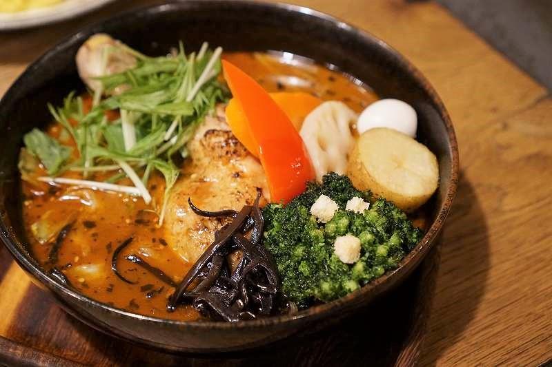チキンレッグと野菜が入ったスープカレーがテーブルに置かれている