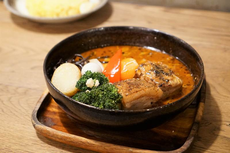 豚角煮と野菜が入ったスープカレーがテーブルに置かれている