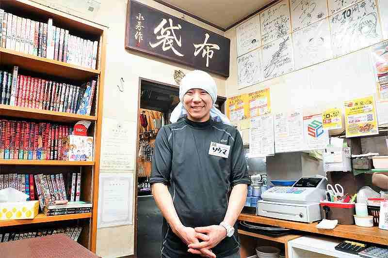 色紙と店名の看板が貼られた店内で笑顔で映る男性