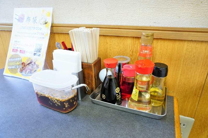 テーブルの上に調味料がのったトレイ、割りばし、ペーパーが置かれている