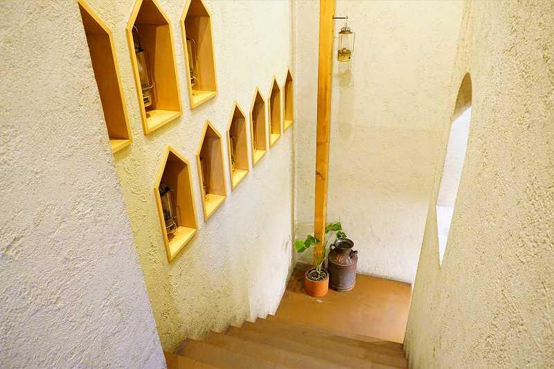 木の装飾がされた白い壁と地下へ続く階段