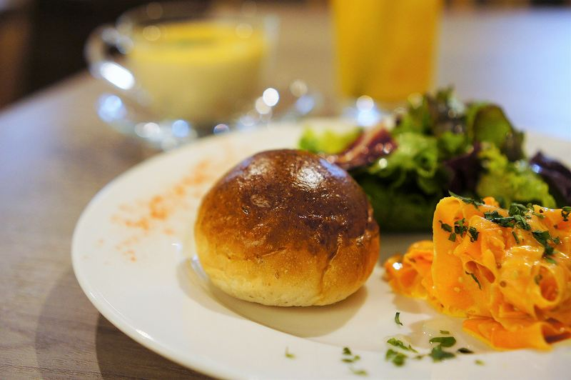 こんがり焼かれた丸いパンと前菜、スープなどがテーブルに置かれている