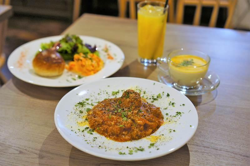パスタ、前菜プレート、ドリンク、スープがテーブルに並んでいる