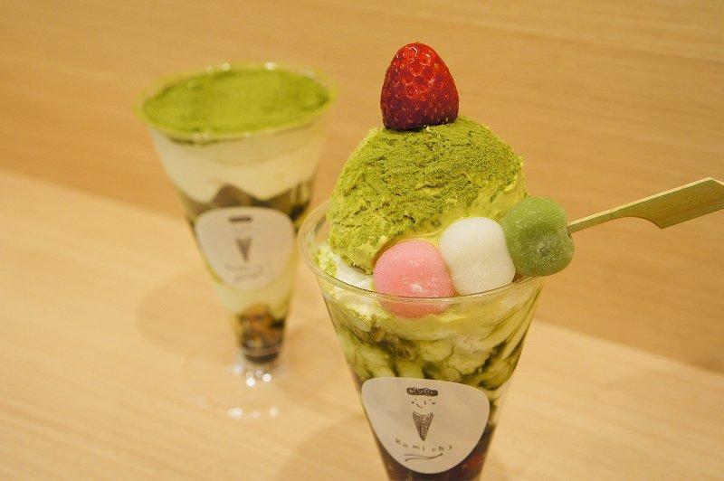 抹茶パウダーでデコレーションされたパフェと、苺、三色団子などがトッピングされたパフェがカウンターに置かれている