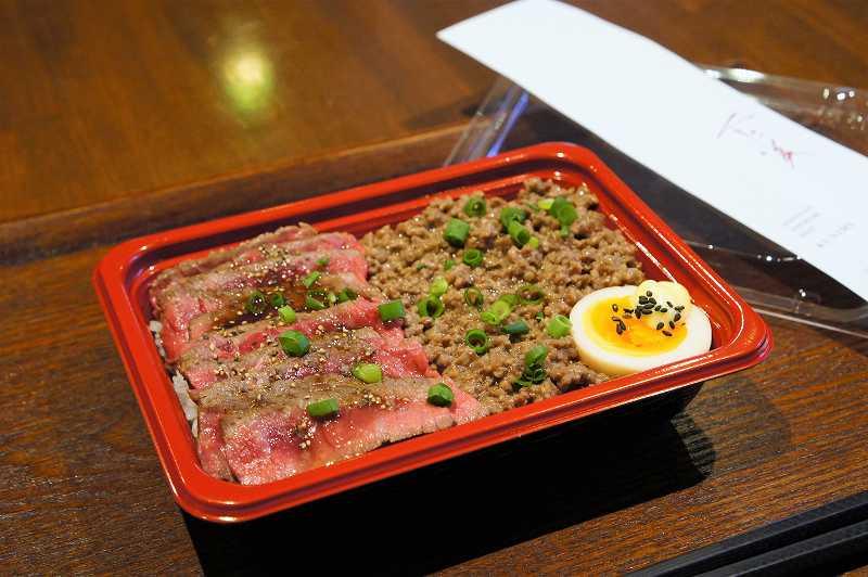 2種類のお肉がのったお弁当がテーブルに置かれている