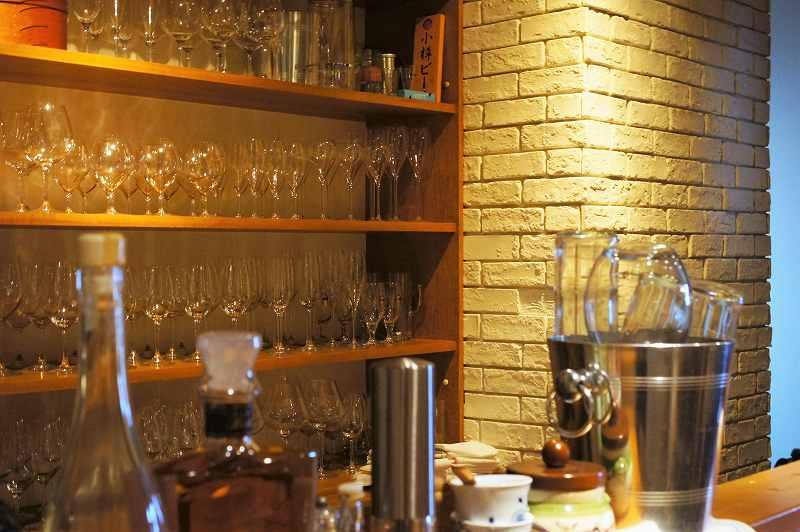 たくさんのグラスが並ぶ棚とお酒のボトルが並ぶカウンター