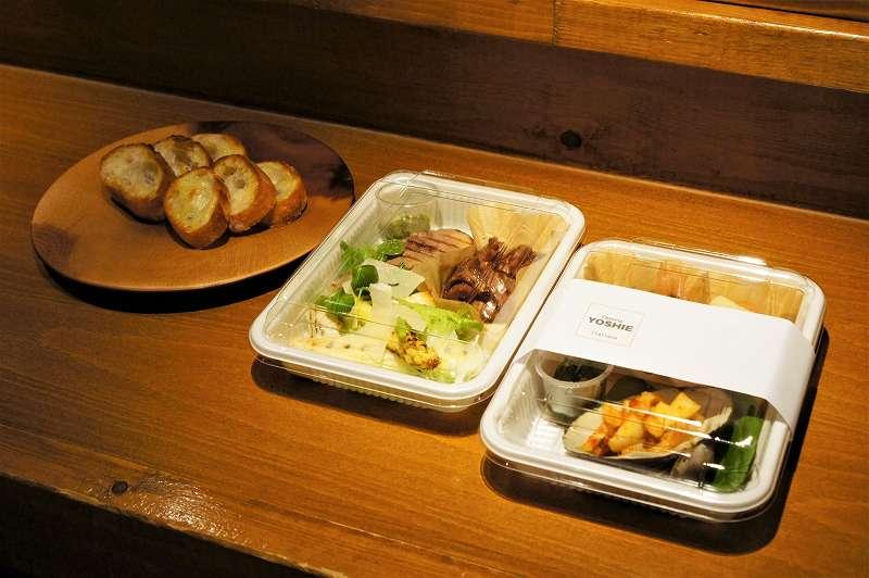 オードブルが入ったプラスチックケース2つとバゲットがのった皿がテーブルに置かれている