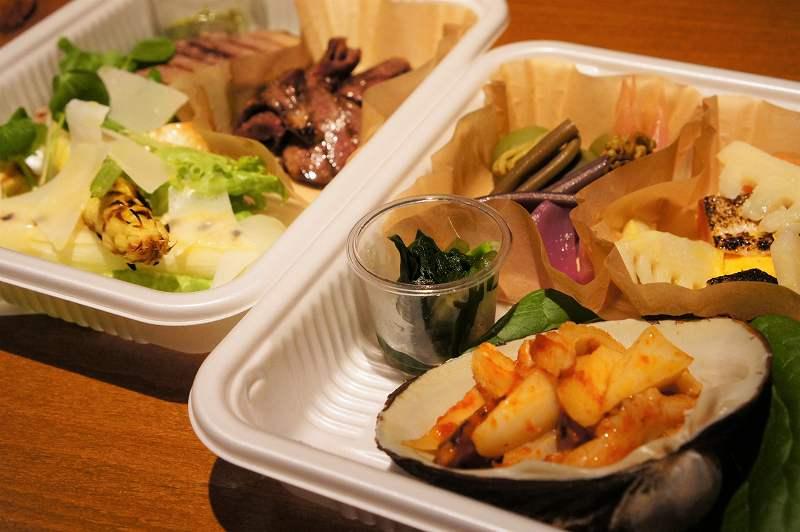貝殻に入ったトマトの和え物、野菜やお肉の1品料理が入ったプラスチックケースがカウンターに置かれいている