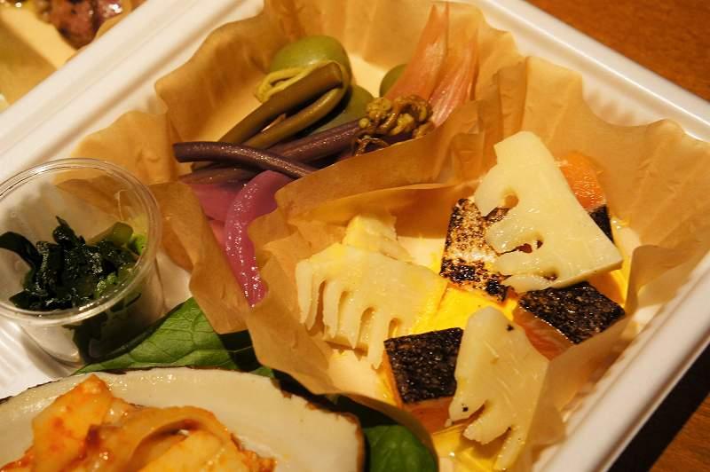 筍、山菜、マスなどを使った前菜がプラスチックケースに入っている