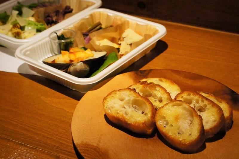 バゲットがのった木の皿と前菜が入ったプラスチックケースがカウンターに置かれている