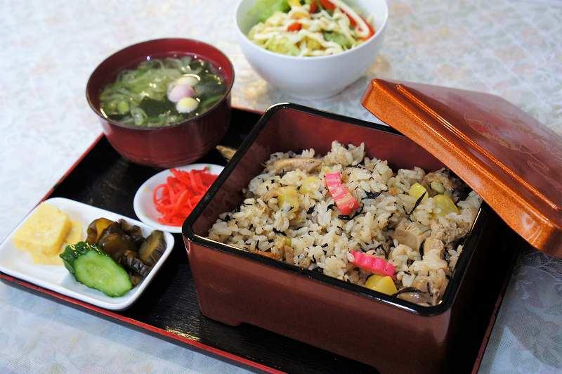 味噌汁、サラダ、重箱に入った五目ごはんがテーブルに置かれている