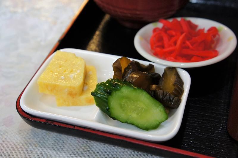 小皿に入った 紅ショウガ、たまご焼き、きゅうりの漬物(2種)がトレイに載せられ、テーブルに置かれている