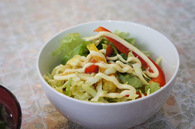 キャベツ、レタス、パプリカが入ったサラダがテーブルに置かれている