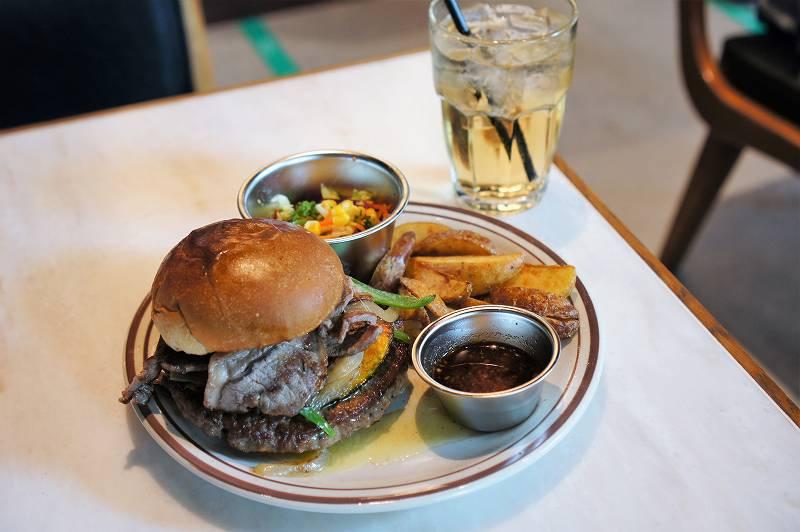グルメバーガー、ポテト、サラダがのったお皿とジンジャーエールがテーブルに置かれている