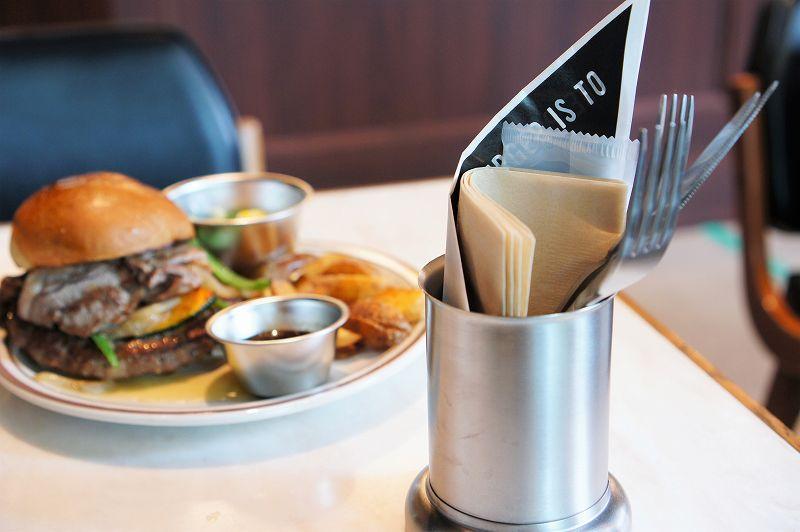 紙ナプキン、カトラリー立てとグルメバーガーがのったお皿がテーブルに置かれている