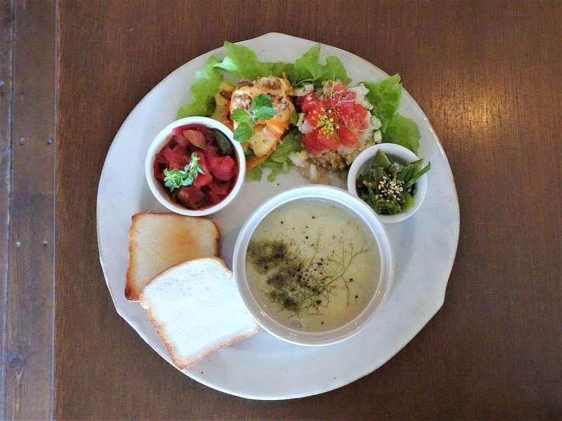 野菜のおかずとパン、スープなどがのったプレートがテーブルに置かれている