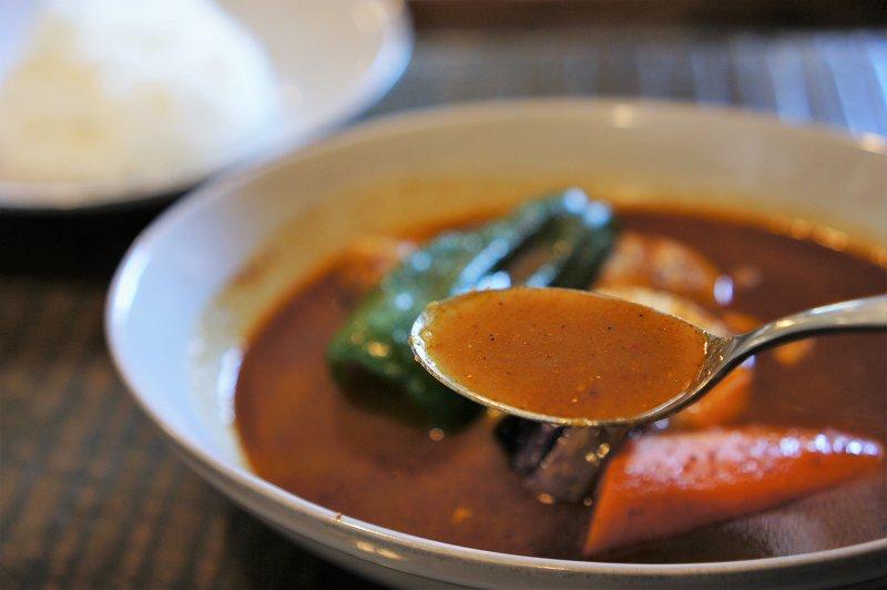 鶏肉と野菜、ゆで卵などが入ったスープカレーをスプーンですくった様子