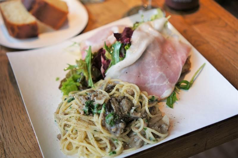 バスタとサラダがのせられた紙皿がテーブルに置かれている