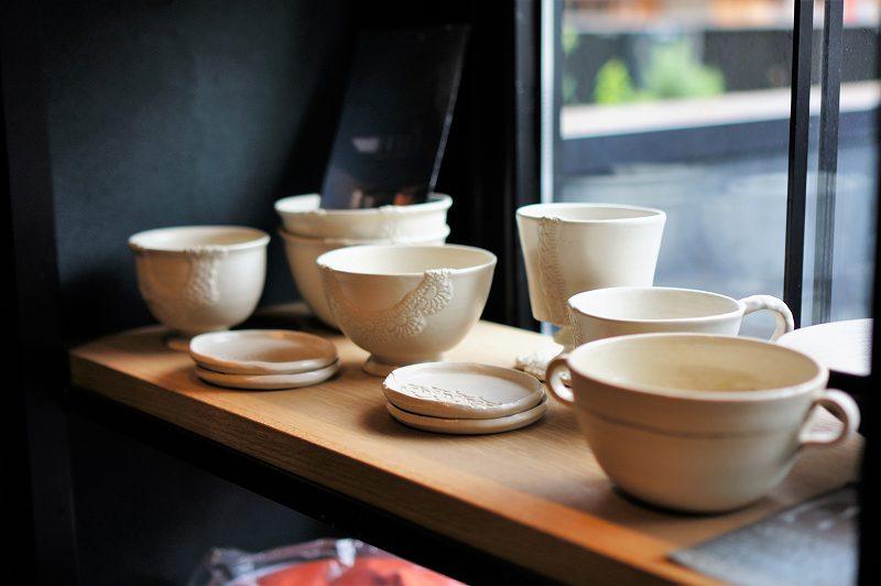 白い陶器のスープカップやプレートなどが棚に置かれている