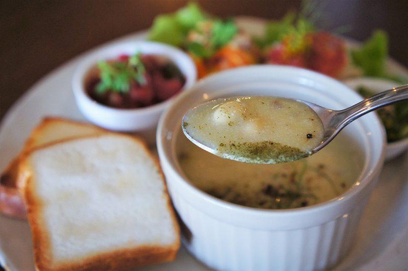 大豆などが入ったポタージュスープをスプーンですくったようす