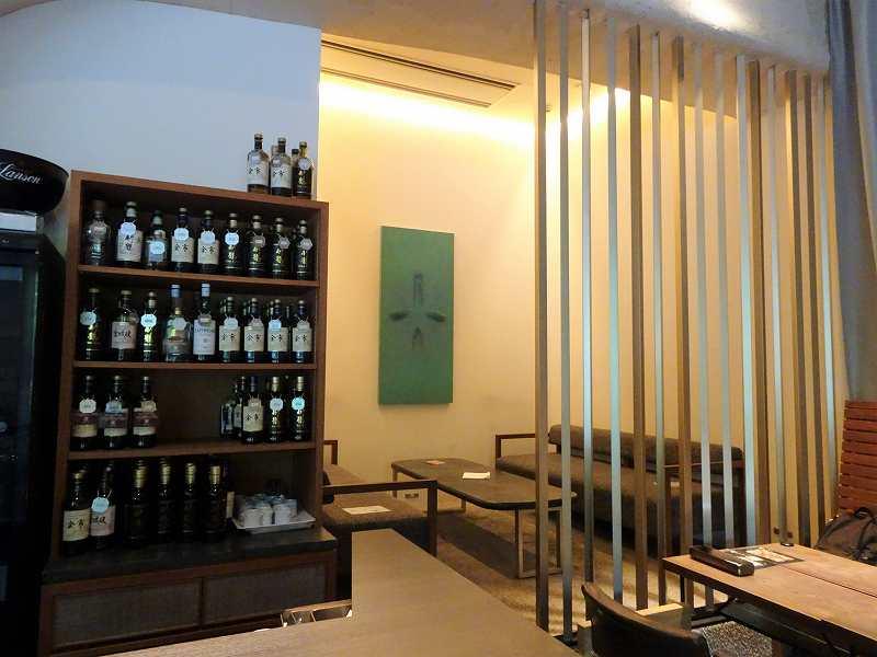 半個室のテーブル席とお酒のボトルが並ぶ棚