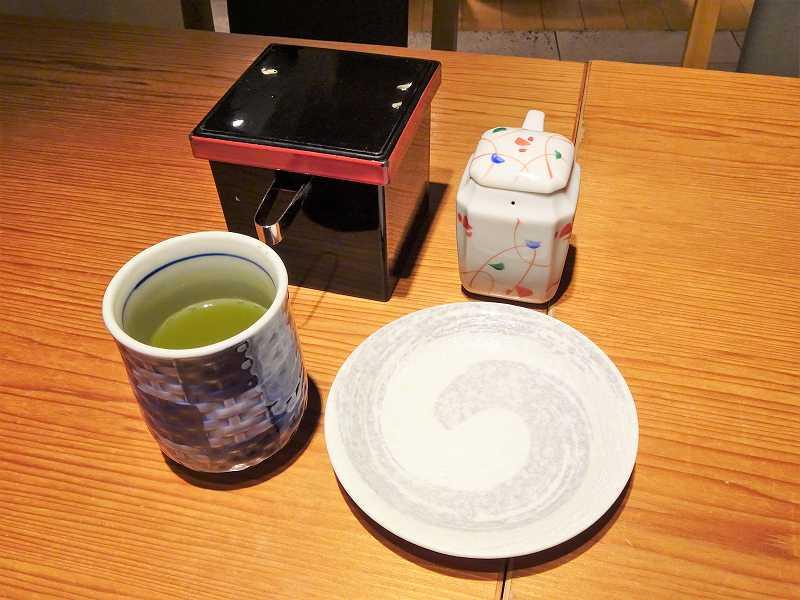 ガリ、醤油、醤油皿、緑茶がテーブルに置かれている