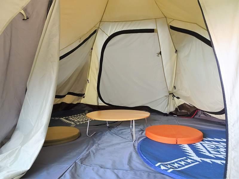 テントの中にテーブルと座布団が置かれている