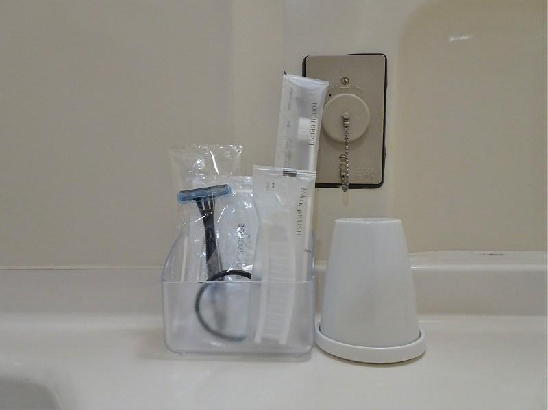 洗面台の上にアメニティとコップが置かれている