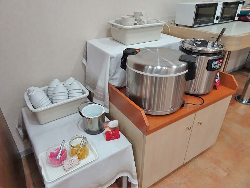 大きな炊飯器やたくさんのお茶碗などが棚に置かれている