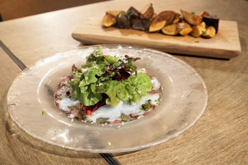 タコのカルパッチョとフライドポテトがテーブルに置かれている
