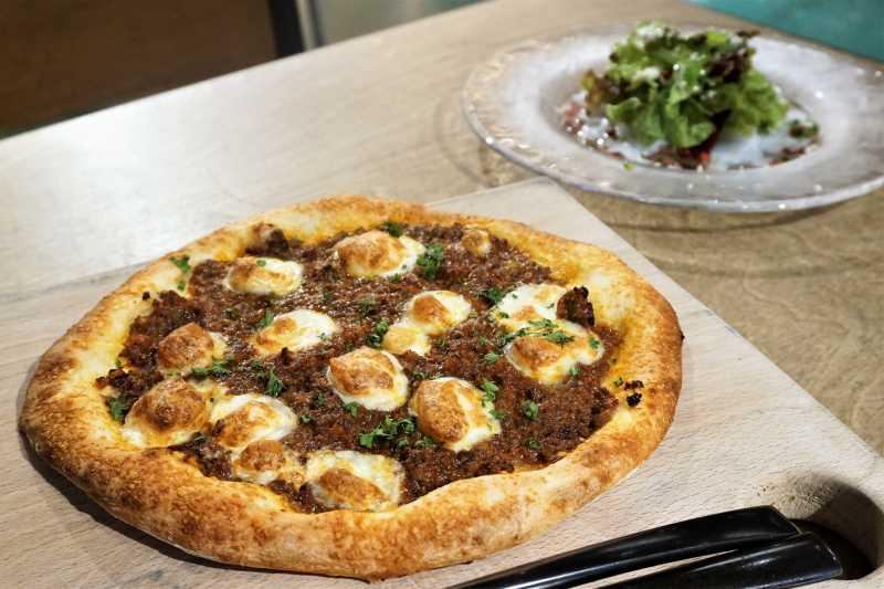 自家製ボロネーゼのピザがテーブルに置かれている