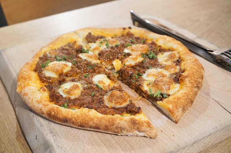 自家製ボロネーゼのピザがカットされ、テーブルに置かれている