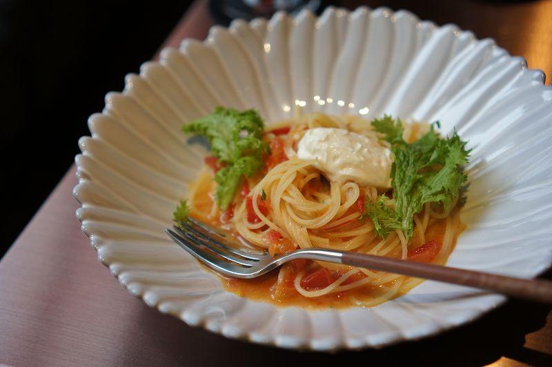 チーズがのったトマトソースパスタがテーブルに置かれている
